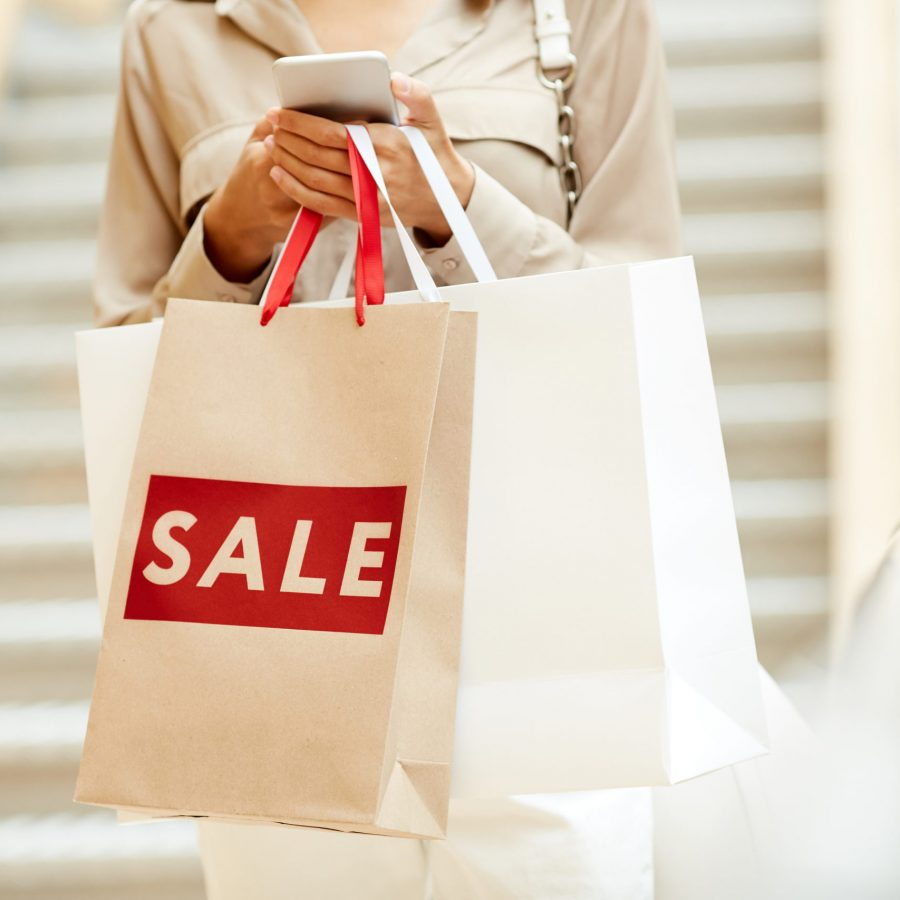 Close-up of young woman with shopping bags typing a message on her mobile phone during sale in the shopping mall